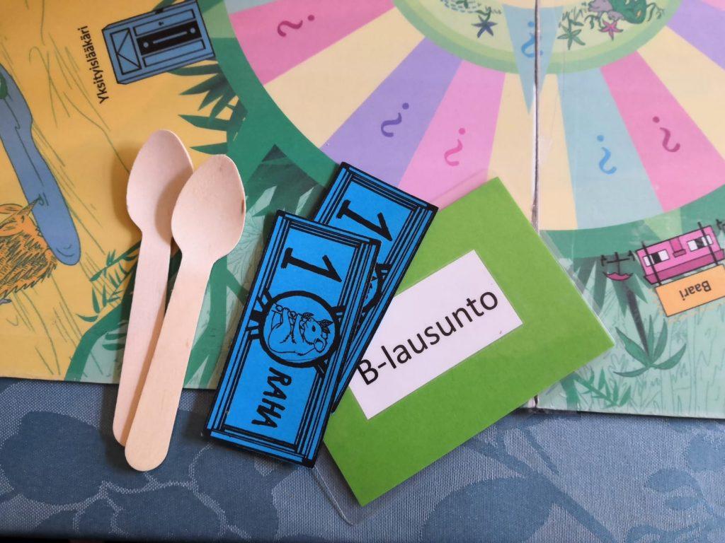 Kaksi puista lusikkaa, kaksi sinistä paperiseteliä ja vihreä B-lausuntokortti Mielenterveysviidakossa-pelilaudalla