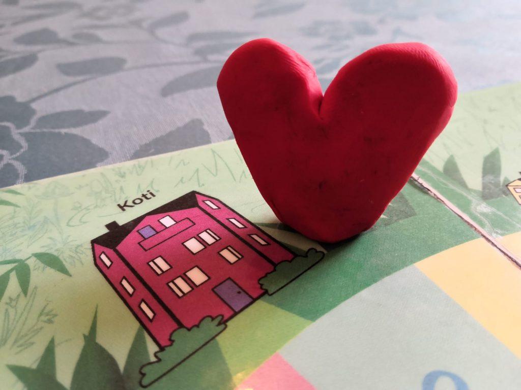 Muovailuvahasta tehty sydämenmuotoinen pelinappula Mielenterveysviidakossa-pelilaudalla punaisessa tehtäväruudussa Koti.