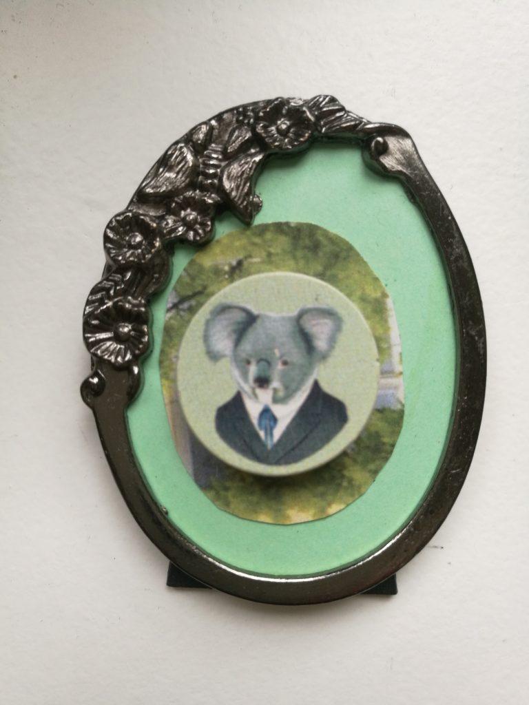 Kuva tummaan pukuun pukeutuneesta koalasta valokuvakehyksissä